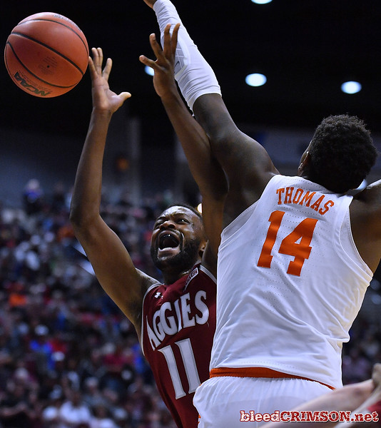 SAN DIEGO, CA - MARCH 16:  Johnathon Wilkins #11 of the New Mexico State Aggies is fouled by Elijah Thomas #14 of the Clemson Tigers during a first round game of the Men's NCAA Basketball Tournament at Viejas Arena in San Diego, California.  (Photo by Sam Wasson)
