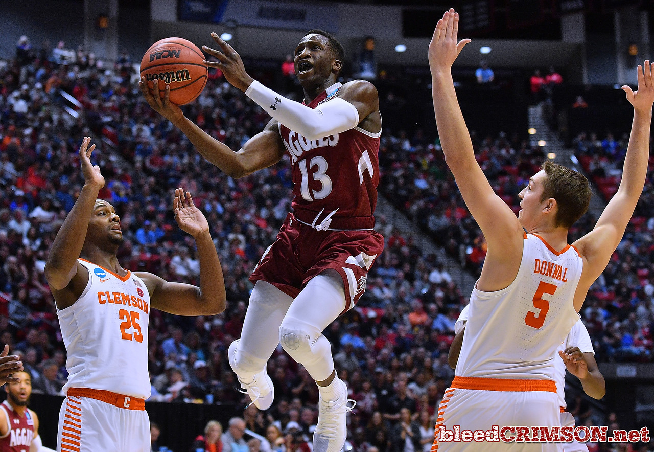 SAN DIEGO, CA - MARCH 16:  Sidy N'Dir #13 of the New Mexico State Aggies drives against Aamir Simms #25 and Mark Donnal #5 of the Clemson Tigers during a first round game of the Men's NCAA Basketball Tournament at Viejas Arena in San Diego, California.  (Photo by Sam Wasson)