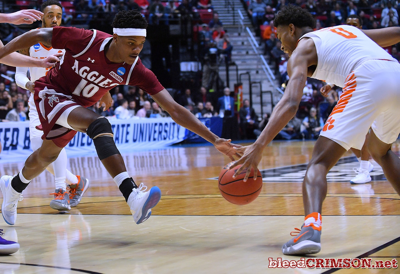 SAN DIEGO, CA - MARCH 16:  Jemerrio Jones #10 of the New Mexico State Aggies loses the ball against Clyde Trapp #0 of the Clemson Tigers during a first round game of the Men's NCAA Basketball Tournament at Viejas Arena in San Diego, California.  (Photo by Sam Wasson)