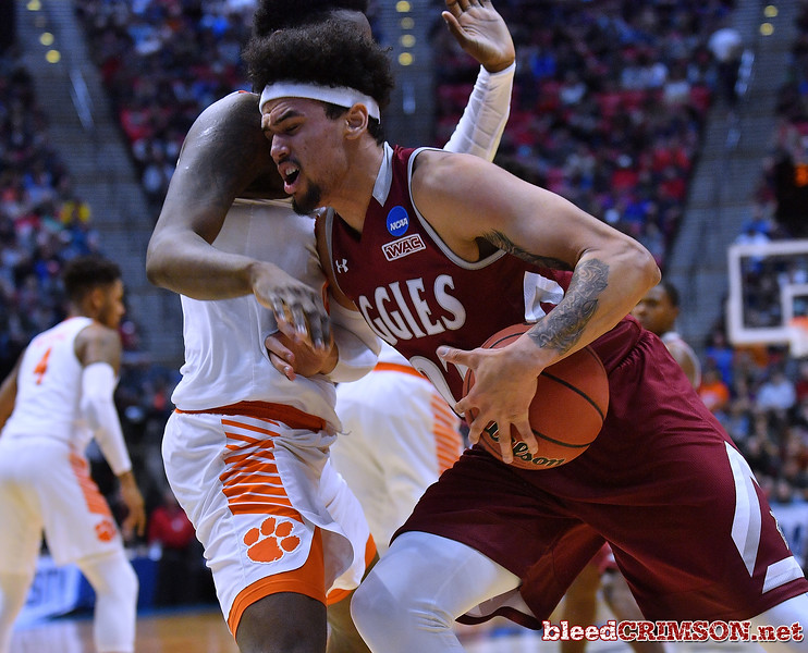 SAN DIEGO, CA - MARCH 16:  Eli Chuha #22 of the New Mexico State Aggies drives to the basket against Elijah Thomas #14 of the Clemson Tigers during a first round game of the Men's NCAA Basketball Tournament at Viejas Arena in San Diego, California.  (Photo by Sam Wasson)