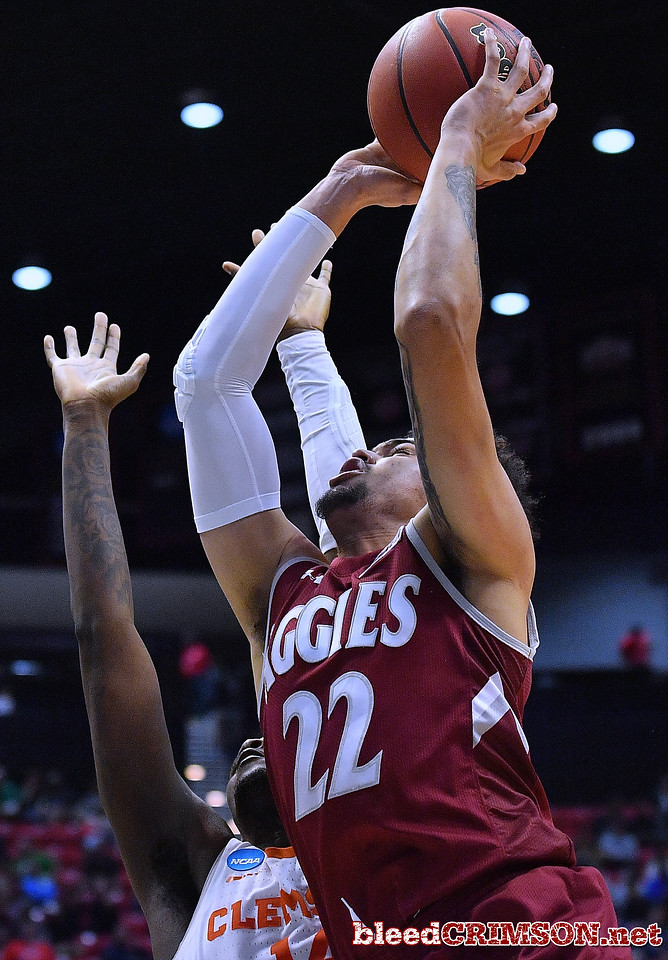 SAN DIEGO, CA - MARCH 16:  Eli Chuha #22 of the New Mexico State Aggies shoots against Elijah Thomas #14 of the Clemson Tigers during a first round game of the Men's NCAA Basketball Tournament at Viejas Arena in San Diego, California. Clemson won 79-68.  (Photo by Sam Wasson)