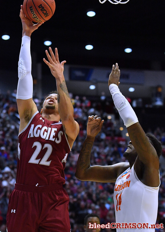 SAN DIEGO, CA - MARCH 16:  Eli Chuha #22 of the New Mexico State Aggies gets a layup against Elijah Thomas #14 of the Clemson Tigers during a first round game of the Men's NCAA Basketball Tournament at Viejas Arena in San Diego, California.  (Photo by Sam Wasson)