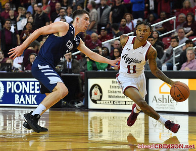 LAS CRUCES, NEW MEXICO - MARCH 05, 2020:  Evan Gilyard #11 of the New Mexico State Aggies drives against Tre Armstrong #3 of the Cal Baptist Lancers during their game at the Pan American Center on March 5, 2020 in Las Cruces, New Mexico. The Aggies defeated the Lancers 83-50 to complete a perfect 16-0 record in WAC play.  (Photo by Sam Wasson/bleedCrimson.net)