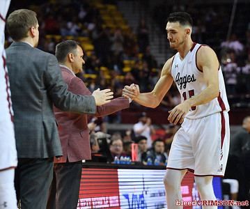 LAS CRUCES, NEW MEXICO - MARCH 05, 2020:  Ivan Aurrecoechea #15 of the New Mexico State Aggies greets head coach Chris Jans after being subbed out during their game against the Cal Baptist Lancers at the Pan American Center on March 5, 2020 in Las Cruces, New Mexico. The Aggies defeated the Lancers 83-50 to complete a perfect 16-0 record in WAC play.  (Photo by Sam Wasson/bleedCrimson.net)