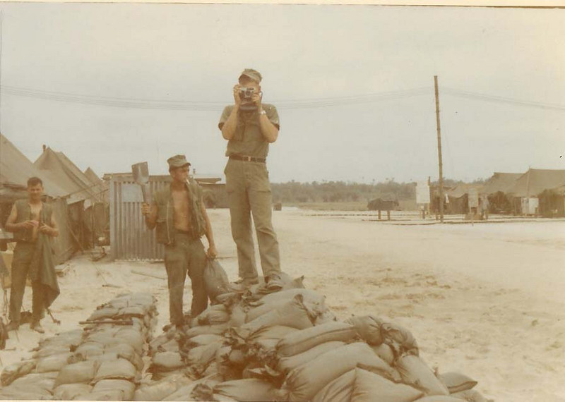 Walter Sweat on the left, unkonwn name in middle, and Dale Ranslem with camera.  Sand bag filling detail.