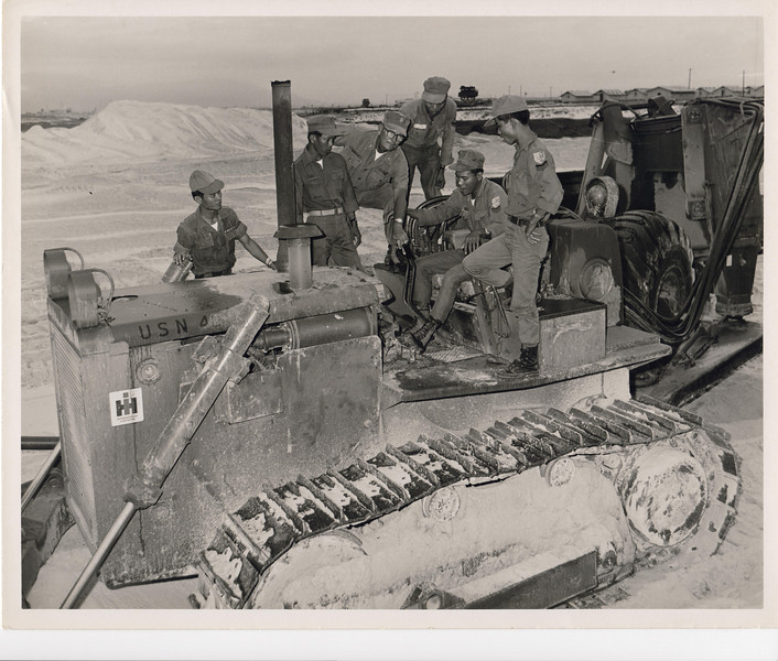 1968 EOC L. Hall, MCB-22, instructs ARVN Combat Engineers on how to operate a crawler tractor.  Photo taken Dec68