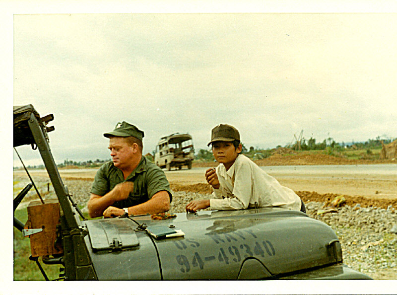 """PO-In-Charge is EO-1 Reardon with his jeep and jobsite """"mascot"""", a local Vietnamese boy"""
