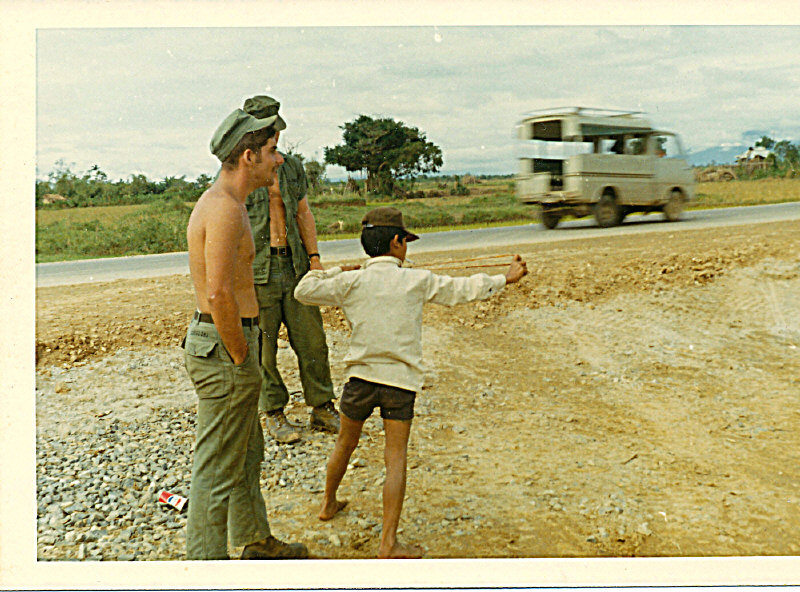 "On QL-1 about 20 miles south of DaNang with jobsite ""mascot"" a local boy. Foreground is Mike Gabrielski-Hidden is Jim Wheat"