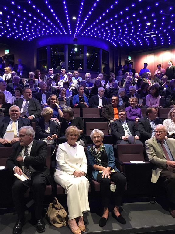 . Seated in the front row of the theater are former MCC President Carole Cowan of Florida and Nancy Donahue of Lowell