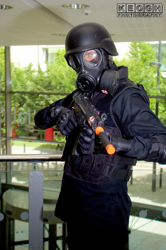 MCM Manchester Comic Con 2016, Cosplayer, Male, Video Game, Comics, Films, Resident Evil, Umbrella Corporation, Racoon City, Military, Soldiers, Military, Guns, Gun, Machine Gun, Utility Belt, Boots, Pants, Trousers, Beret, Glasses, Cap, Gas Mask, Respiratory Mask, Shirt, Jacket, Bullet Proof, Bags, Black, Red, White