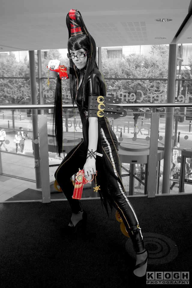MCM Manchester Comic Con 2016, Cosplay, Cosplayer, Female, Video Game, Bayonetta, Sega, Witch, Sorceress, Hero, Anti-Hero, Guns, Spiritual, Jumpsuit, Gloves, High Heels, Boots, Chains, Glasses, Head Dress, Straps, Black, White, Red, Gold, Wig