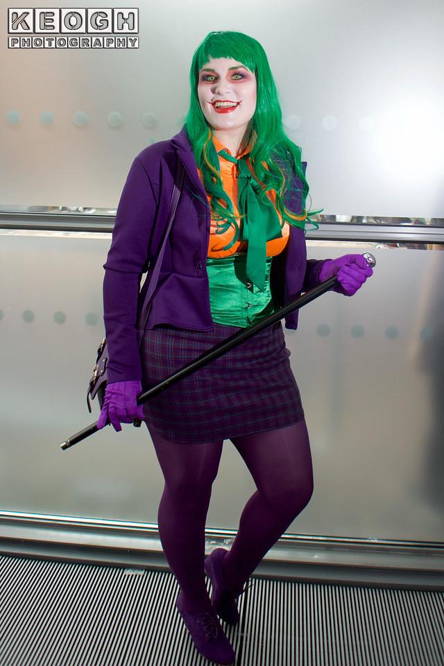 MCM Manchester Comic Con 2016, Cosplay, Cosplayer, Female, The Joker, Batman, Mistah J, Pudding, Villain, Psychopath, Master Criminal, Insane, Jacket, Blouse, Corset, Tie, Bow, Skirt, Tartan, Tights, High Heels. Handbag, Gloves, Cane, Walking Cane, Chattering Teeth, Wig, Purple, Green, Orange, White, Red, Black