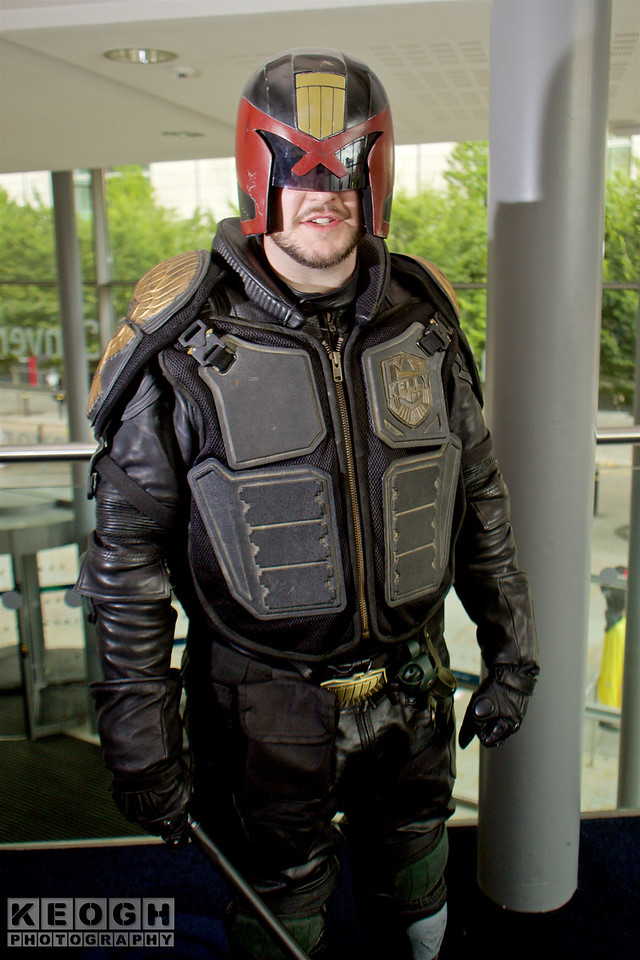 MCM Manchester Comic Con 2016, Cosplay, Cosplayer, Male, Comics, Films, Video Games, Judge Dredd, 2000AD, Mega City One, Police Officer, Law Enforcer, Military, Hero, Helmet, Armour, Jacket, Gloves, Pants, Boots, Badge, Bullet Proof Jacket, Baton, Truncheon, Leather, Metal, Black, Grey, Gold, Belt, Red