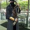 MCM Manchester Comic Con 2016, Cosplay, Cosplayer, Male, Video Game, Bloodbourne, Hunter, Cowboy, Steampunk, Hat, Mask, Waistcoat, Straps, Arm Guards, Pants, Gun, Scythe, Black, Brown, Silver, Gold, Blade