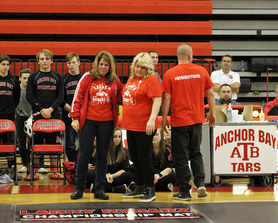 . Marina Rybarz, left, and her daughter, Kelly Parada, look at the Larry Rybarz Championship Mat that was dedicated in memory of the former Anchor Bay wrestler. Marina Rybarz, Larry\'s mother, and Parada, his sister, attended the dedication ceremony with other family members prior to a four-team meet. THE MACOMB DAILY PHOTO GALLERY BY GEORGE SPITERI.
