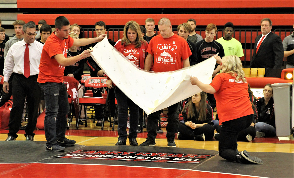 . Eric Rybarz, left, and Kelly Parada, brother and sister of the late Larry Rybarz III, unveil the new Anchor Bay wrestling mat that was dedicated to the memory of their brother. Rybarz III, who won more than 200 matches at Anchor Bay, died in an automobile accident in August at the age of 24. THE MACOMB DAILY PHOTO GALLERY BY GEORGE SPITERI.