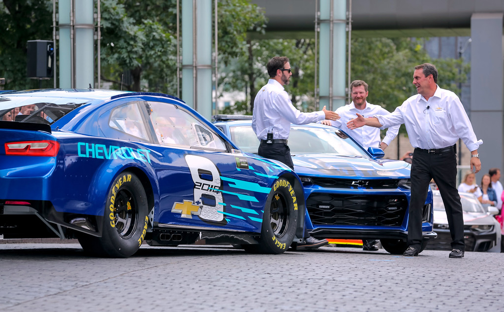 . Seven-time NASCAR Cup champion Jimmie Johnson (l to r) and Hendrick Motorsports teammate Dale Earnhardt Jr. are greeted by General Motors Executive Vice President Global Product Development Mark Reuss as Johnson drives up in the Chevrolet 2018 Camaro ZL1 NASCAR Cup Race Car at its world debut in Detroit.