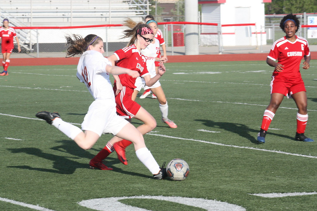 . Chippewa Valley\'s Alexa Barczak attempts to boot the ball past Cousino\'s Emma Rutkowski during the first half of their MAC Blue Division match on May 14, 2018 at Chippewa Valley. (Photo gallery by Kevin Lozon)