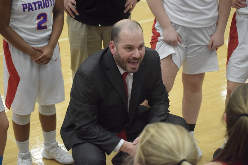 Coach Mike Lee and the Cousino Patriots huddle. Cousino defeated Sterling Heights 57-14 in a Class A girls district basketball championship game at Warren Woods-Tower on Friday, March 2.  THE MACOMB DAILY PHOTO GALLERY BY GEORGE POHLY