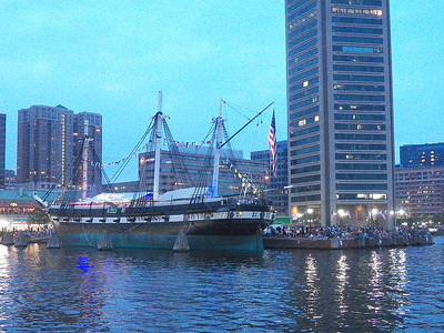 the USS Constellation and the base of the Baltimore World Trade Center as well as crowds of people waiting for the fireworks