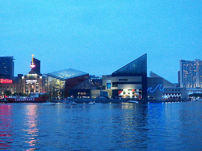 the Inner Harbor at dusk with the Power Plant on the left and  the National Aquarium in the center