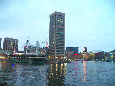 the Inner Harbor at dusk - from left to right - the USS Constellation, the Baltimore World Trade Center, the Power Plant, the National Aquarium