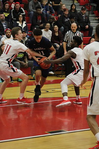 Dakota's Ryan Rollins attempts to dribble between Chippewa Valley's Dennis Pozios (11) and Devin Goodwyn during their game on January 26, 2018. (Photo gallery by Kevin Lozon)