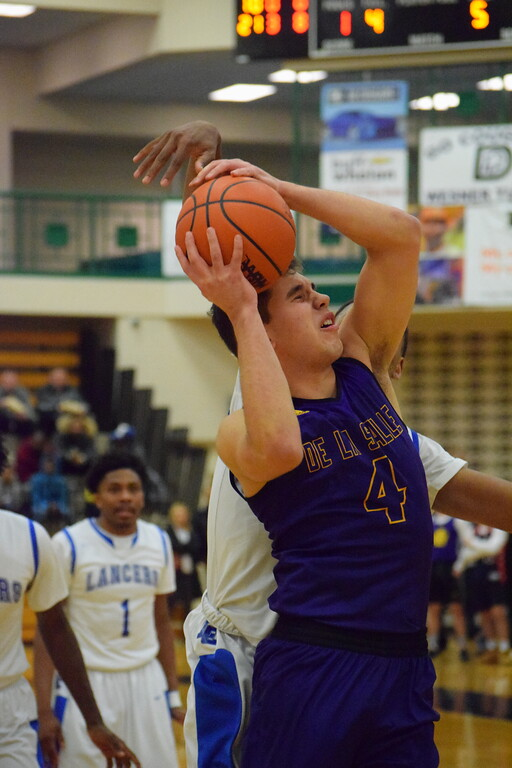 . De La Salle\'s Kole Gjonaj (4) is fouled on his way to the basket in the Pilots\' 75-60 win over L\'Anse Creuse in a Class A regional boys basketball semifinal at Dakota on March 12, 2017. THE MACOMB DAILY PHOTO GALLERY BY CHUCK PLEINESS