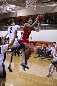 Lake Shore's Melik Miner attempts a layup while receiving contact from Utica's Trey Koteles during the first quarter of the MAC Blue Division game on January 11, 2019. (Photo gallery by Kevin Lozon)