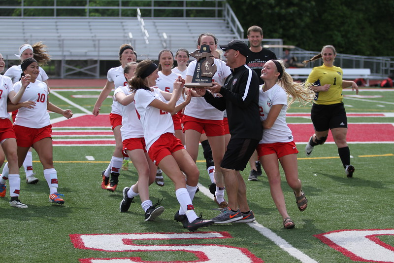 Lake Shore players mob coach David Lount and the Division 1 district championship trophy Saturday afternoon. For the Shorians, the district title is their first in girls soccer in school history. (Photo by Bill Roose)