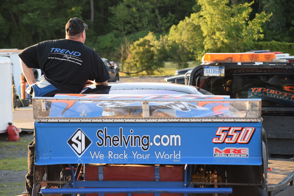 . Terry Bogusz rides on a flatbed truck with his damaged Late Model race car after an accident at Flat Rock Speedway. Bogusz, a Shelby Township resident, started the race on the pole position.
