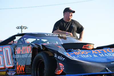 Terry Bogusz rides with his damaged Late Model race car after a broken axle sent the Shelby Township driver head-on into the wall during a race at Flat Rock Speedway.