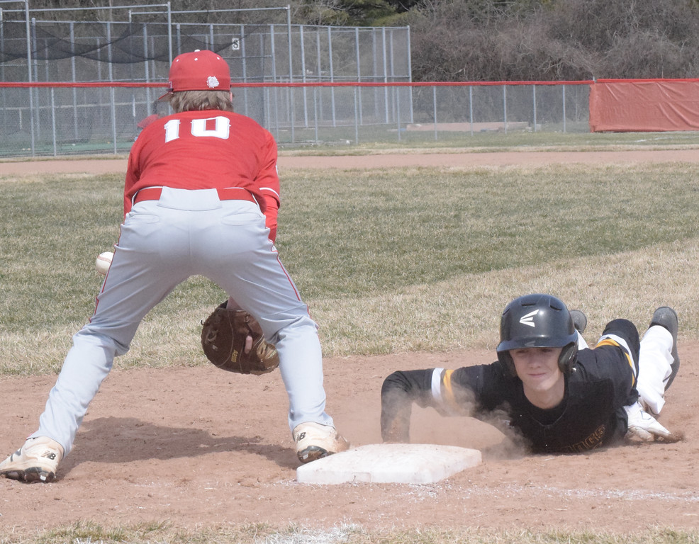 . Brendan Herbst of Lutheran North dives safely back to first base as Romeo\'s Kaden Stively awaits a throw during a non-league game.