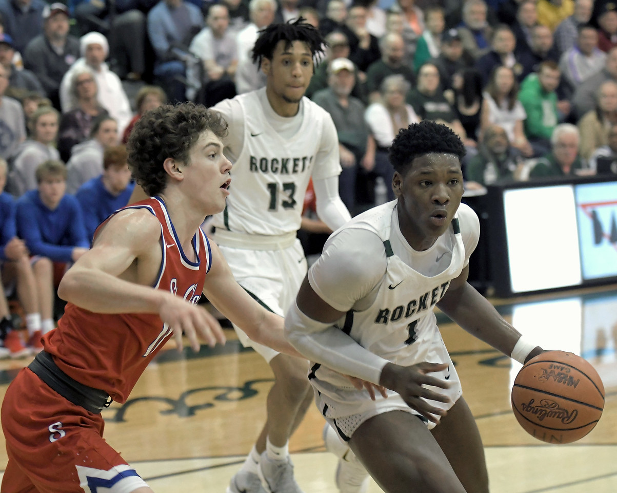 Romeo Weems (1) of New Haven moves past Mario Mattson (10) of St. Clair during the match between New Haven and St. Clair on March 12, 2018.  MACOMB DAILY PHOTO GALLERY BY DAVID DALTON