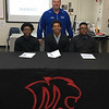 Michigan Collegiate wrestlers, from left, Tanell McCalebb, Roderick Fletcher and DeShawn Broadus sign with Henry Ford Community College.