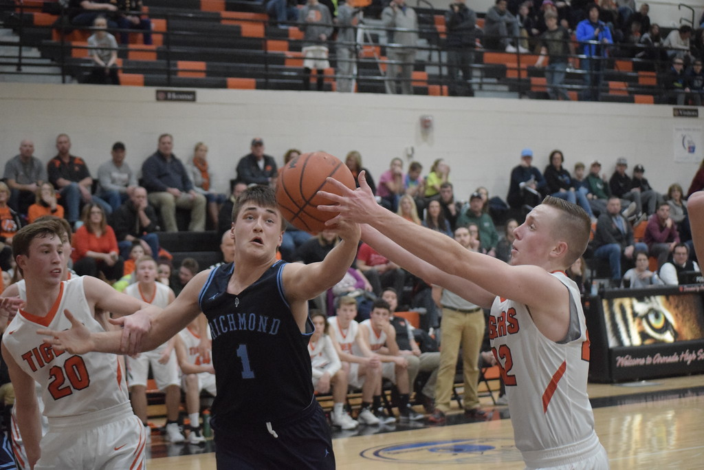 . Connor Cracchiolo of Richmond and Mitch Ruczynski of Armada reach for the ball during the first quarter. Armada defeated Richmond 55-44 in a key Blue Water Area Conference basketball game played on the Tigers\' floor Tuesday, Feb. 13.  THE MACOMB DAILY PHOTO GALLERY BY GEORGE POHLY