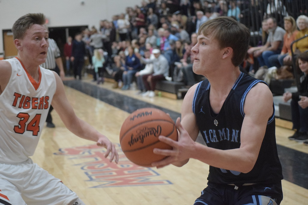 . Chase Churchill of Richmond lines up a shot as Cameron Hart of Armada closes in during the first quarter. Armada defeated Richmond 55-44 in a key Blue Water Area Conference basketball game played on the Tigers\' floor Tuesday, Feb. 13.  THE MACOMB DAILY PHOTO GALLERY BY GEORGE POHLY