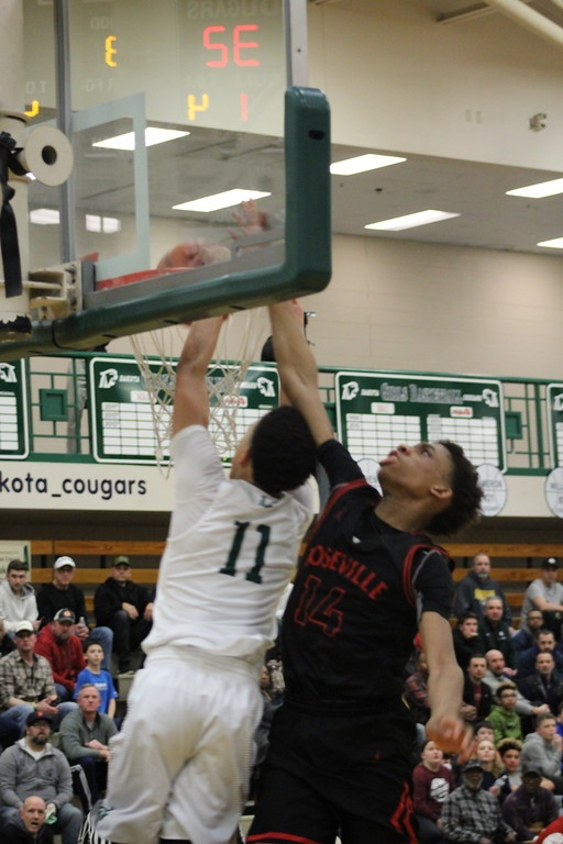 . Dakota\'s Ryan Rollins dunks the ball over Roseville\'s John Ukomadu during their Class A regional championship game at Dakota on March 12, 2018. (Photo gallery by Kevin Lozon)
