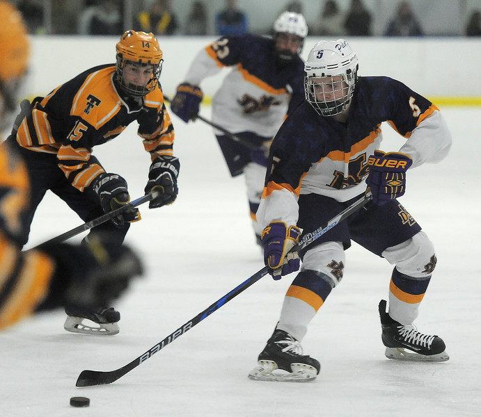 Jordan Kovacs (5) of De La Salle battles for control of the puck during the game between De La Salle and Trenton on December 21, 2016. (MIPrepZone photo gallery by David Dalton)