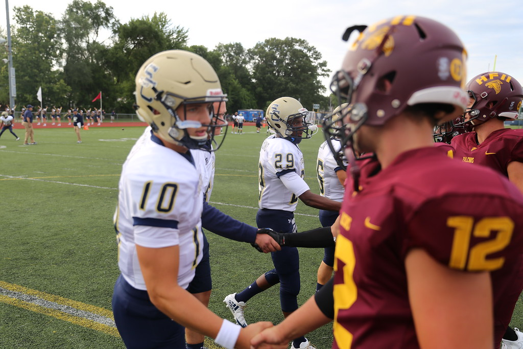 . Stoney Creek junior quarterback Frank Potenza (10) introduces himself to Utica Ford QB Noah Heide (12) before Thursday\'s coin toss. (Photo by Bill Roose)