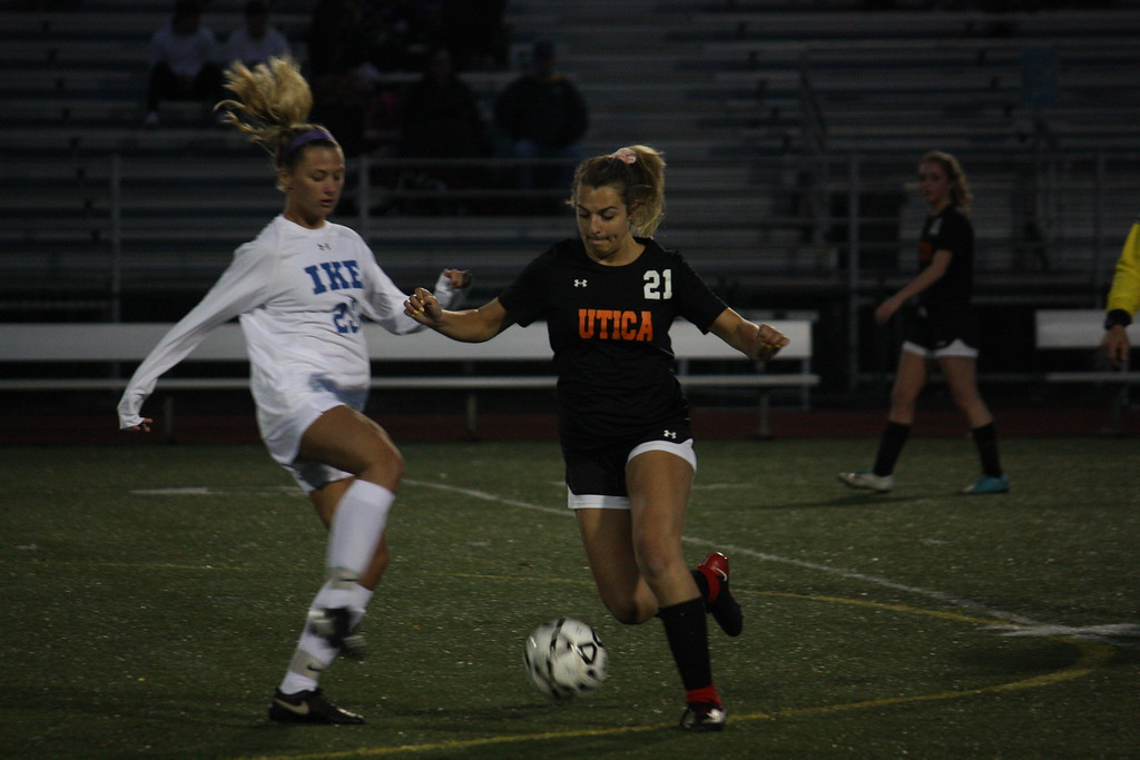. Utica\'s Cassidy Hough attempts to dribble past  Eisenhower\'s Anna McIntosh during the first half of their MAC crossover game on April 11, 2018. (Photo gallery by Kevin Lozon)