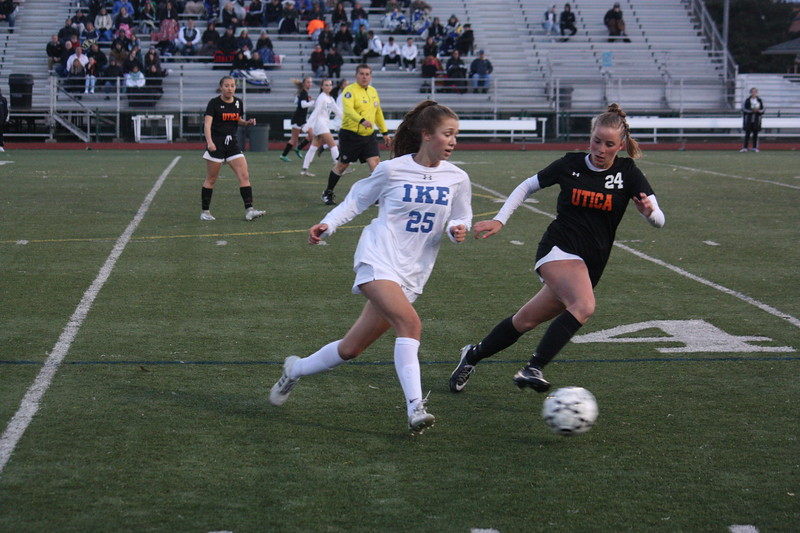 Eisenhower's Lauren DeBeau attempts to dribble past Utica's Emily Lorkowski during their MAC crossover match at Utica High School on April 11, 2018. (Photo gallery by Kevin Lozon)