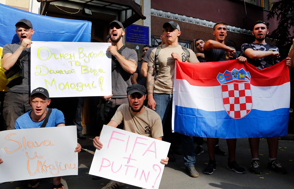 """. Activists hold posters and a Croatian flag in support of Croatia defender Domagoj Vida in front of Croatia\'s Embassy in Kiev, Ukraine, Tuesday, July 10, 2018. FIFA has issued a formal warning to Vida who praised Ukraine in a video after his team beat World Cup host Russia, saying \'glory to Ukraine\'. Writing on the upper poster reads: \""""Ognjen Vukojevic and Domagoj Vida, well done!\' (AP Photo/Efrem Lukatsky)"""