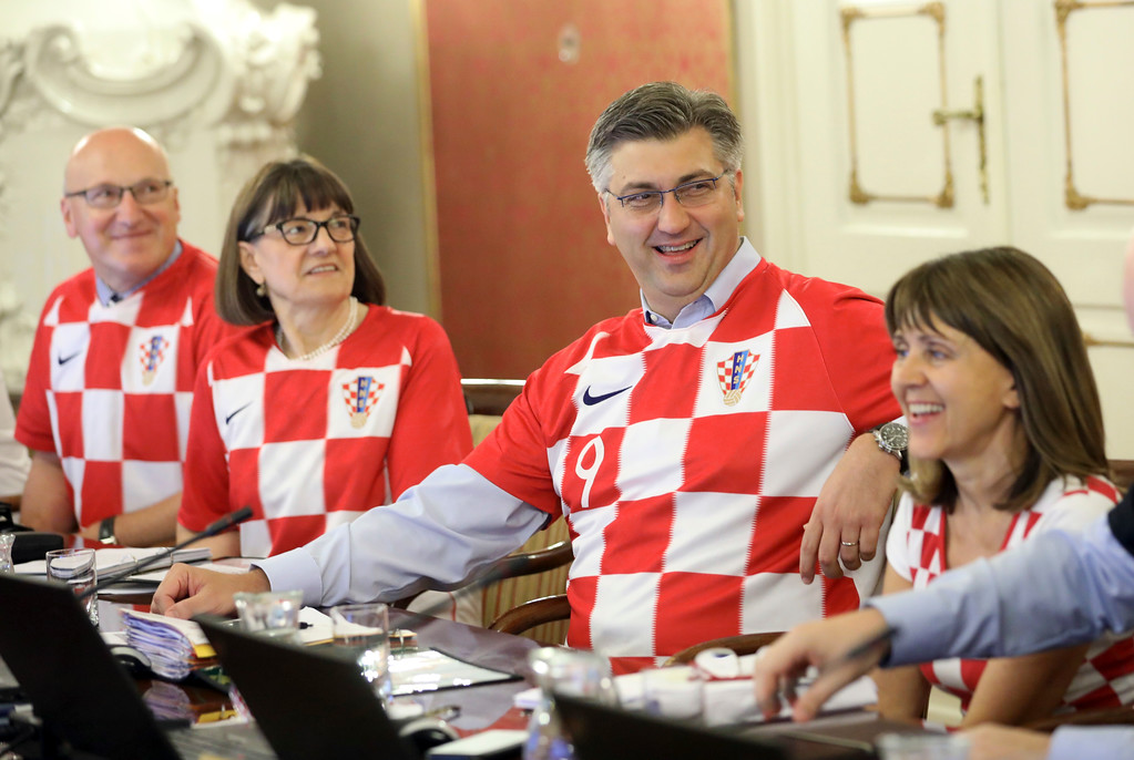 . Croatia\'s Prime Minister Andrej Plenkovic, center, sits between ministers wearing Croatian national soccer team jerseys during during a government session in Zagreb, Croatia, Thursday, July 12, 2018, a day after Croatia qualified in finals at the soccer World Cup. (AP Photo)