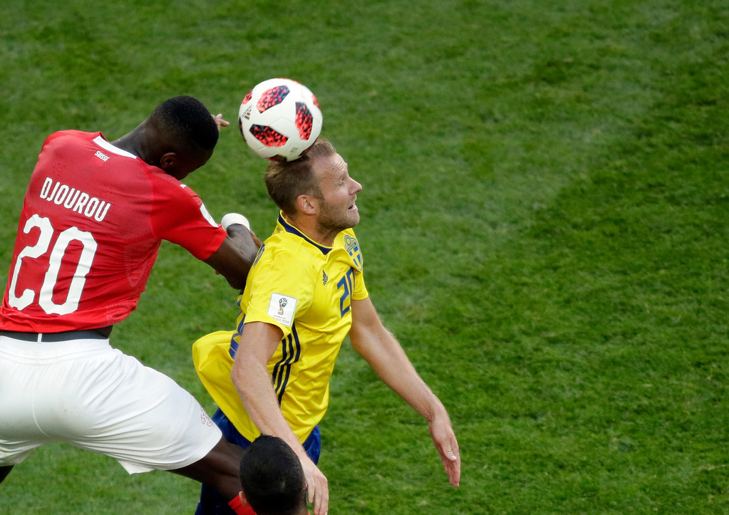 . Switzerland\'s Johan Djourou, left, jumps for the ball with Sweden\'s Ola Toivonen during the round of 16 match between Switzerland and Sweden at the 2018 soccer World Cup in the St. Petersburg Stadium, in St. Petersburg, Russia, Tuesday, July 3, 2018. (AP Photo/Dmitri Lovetsky)
