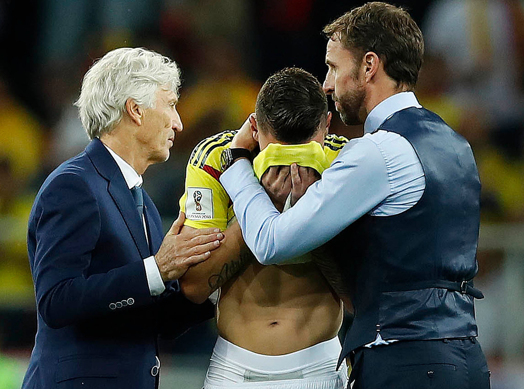 . Colombia head coach Jose Pekerman, left, and England head coach Gareth Southgate, right, comfort Colombia\'s Mateus Uribe after the round of 16 match between Colombia and England at the 2018 soccer World Cup in the Spartak Stadium, in Moscow, Russia, Tuesday, July 3, 2018. (AP Photo/Alastair Grant)