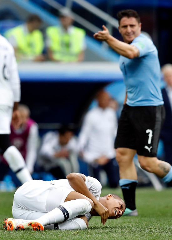 . Uruguay\'s Cristian Rodriguez, rear, reacts as France\'s Kylian Mbappe, front, lies on the pitch during the quarterfinal match between Uruguay and France at the 2018 soccer World Cup in the Nizhny Novgorod Stadium, in Nizhny Novgorod, Russia, Friday, July 6, 2018. France defeated Uruguay by 2-0. (AP Photo/David Vincent)