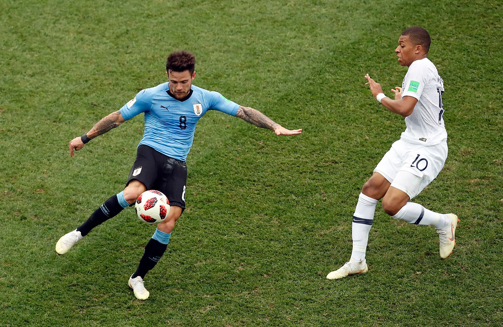 . Uruguay\'s Nahitan Nandez clears the ball away from France\'s Kylian Mbappe during the quarterfinal match between Uruguay and France at the 2018 soccer World Cup in the Nizhny Novgorod Stadium, in Nizhny Novgorod, Russia, Friday, July 6, 2018. (AP Photo/Hassan Ammar)