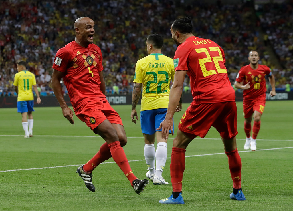 . Belgium\'s Vincent Kompany, left, and Nacer Chadli celebrate after Brazil\'s Fernandinho scored an own goal during the quarterfinal match between Brazil and Belgium at the 2018 soccer World Cup in the Kazan Arena, in Kazan, Russia, Friday, July 6, 2018. (AP Photo/Andre Penner)