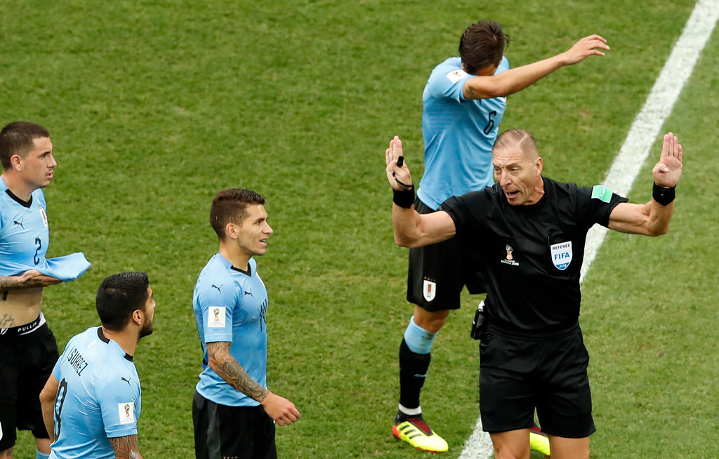 . Referee Nestor Pitana right, gestures to the Uruguayan players during the quarterfinal match between Uruguay and France at the 2018 soccer World Cup in the Nizhny Novgorod Stadium, in Nizhny Novgorod, Russia, Friday, July 6, 2018. (AP Photo/Hassan Ammar)